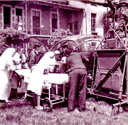 A l'hôpital d'Annecy, Francis RIERA (Pilote) et Paul ROUET (Mécanicien) chargent un blessé pour une évacuation avec l' Alouette 2 F-ZBAC Protection civile de la Base d'Annecy le 30 mai 1964 - Photo DR Archives GHSC Base d'Annecy